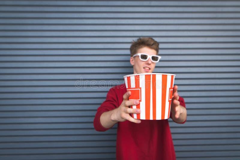Homem novo nos vidros 3D, na camiseta vermelha e em um grande copo de suportes da pipoca no fundo de uma parede escura fotografia de stock