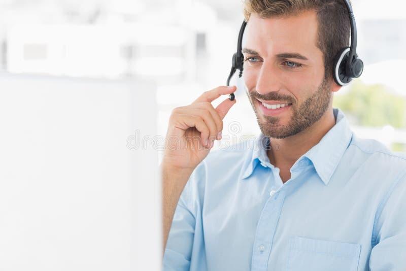 Homem novo ocasional com auriculares usando o computador fotos de stock