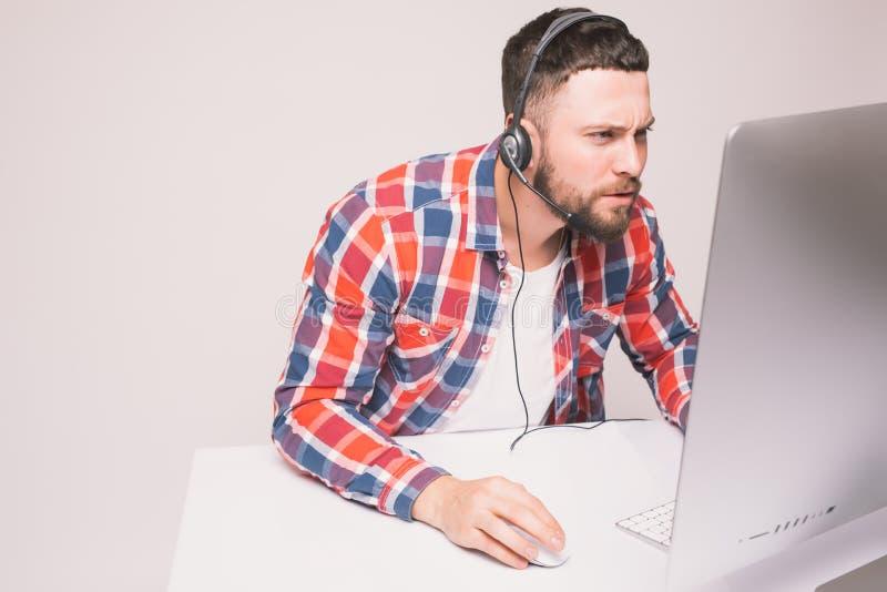 Homem novo ocasional com auriculares usando o computador em um escritório brilhante fotografia de stock