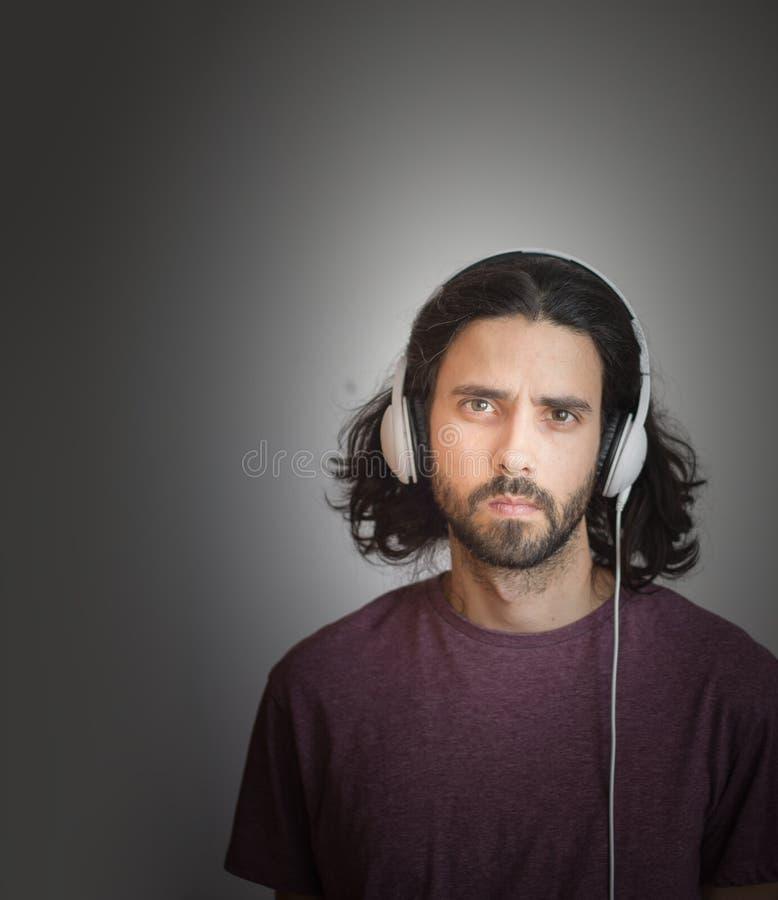 Homem novo ocasional com fones de ouvido imagem de stock royalty free