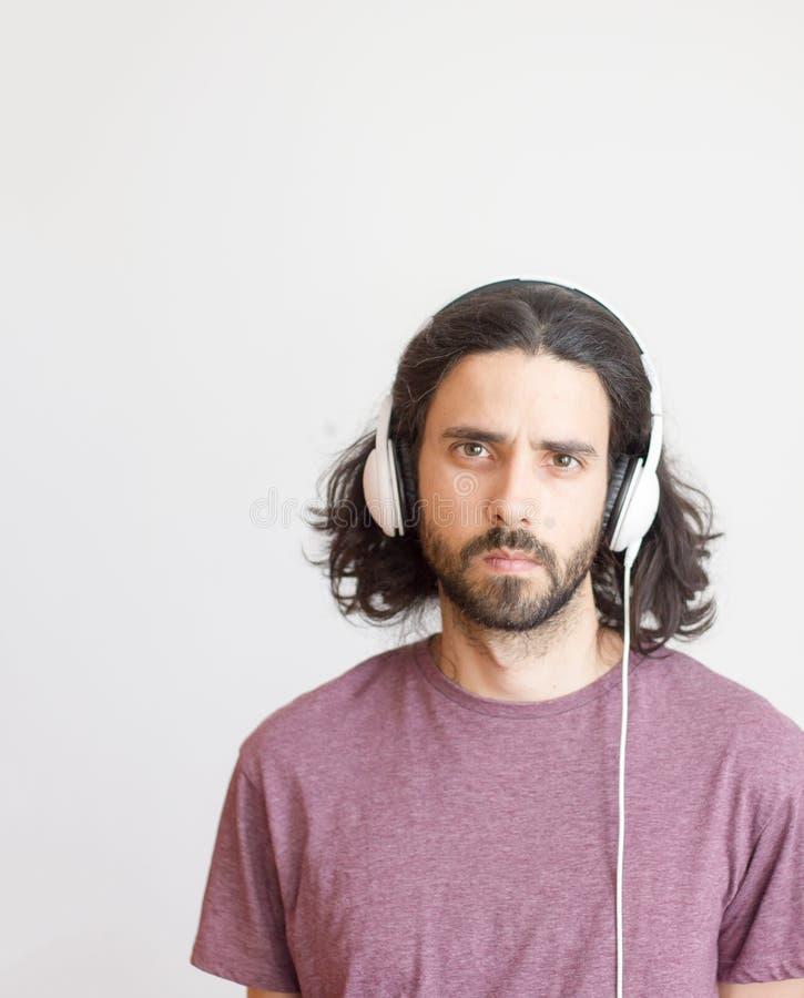 Homem novo ocasional com fones de ouvido fotos de stock royalty free