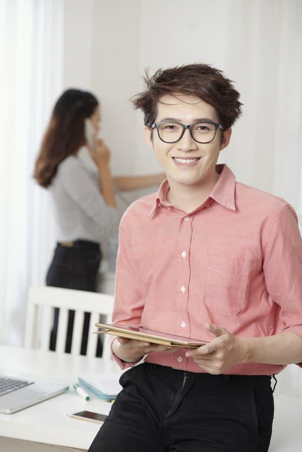 Homem novo ocasional com a tabuleta no escritório imagem de stock royalty free