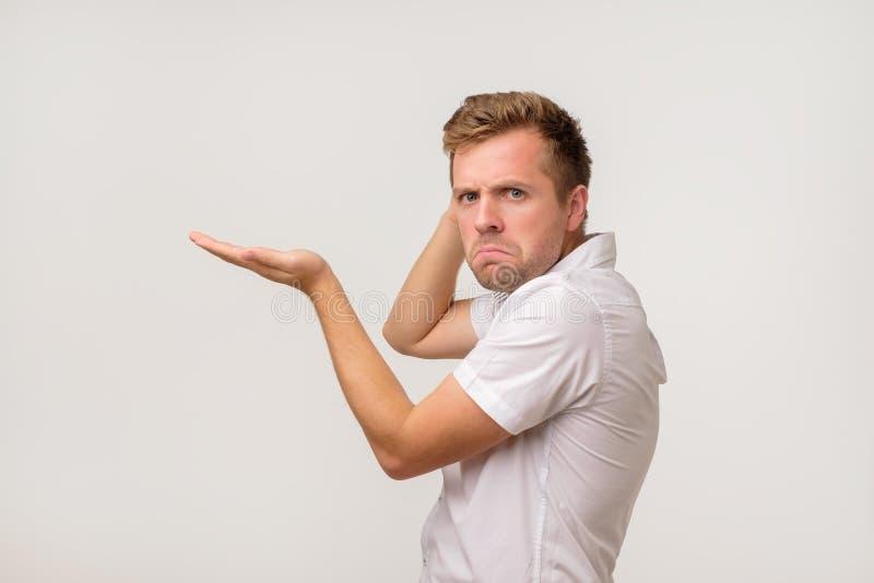 Homem novo ocasional confuso atrativo na camisa que guarda o copyspace na palma fotos de stock royalty free