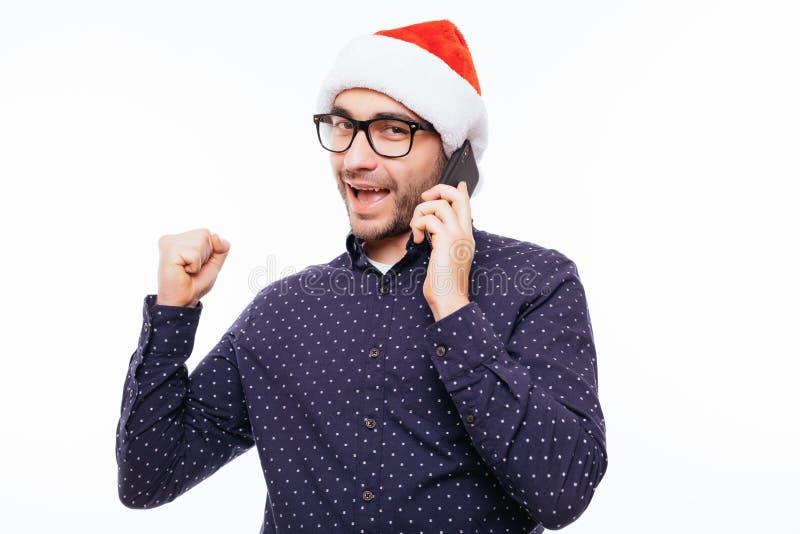 Homem novo ocasional no chapéu de Santa que fala no telefone e no cheering Isolado em um fundo branco fotos de stock