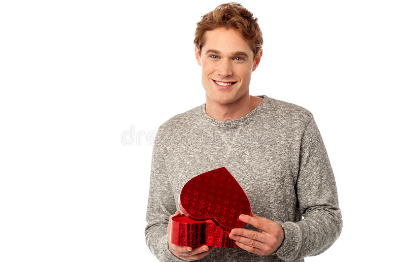 Homem novo ocasional que abre seu presente do Valentim imagens de stock