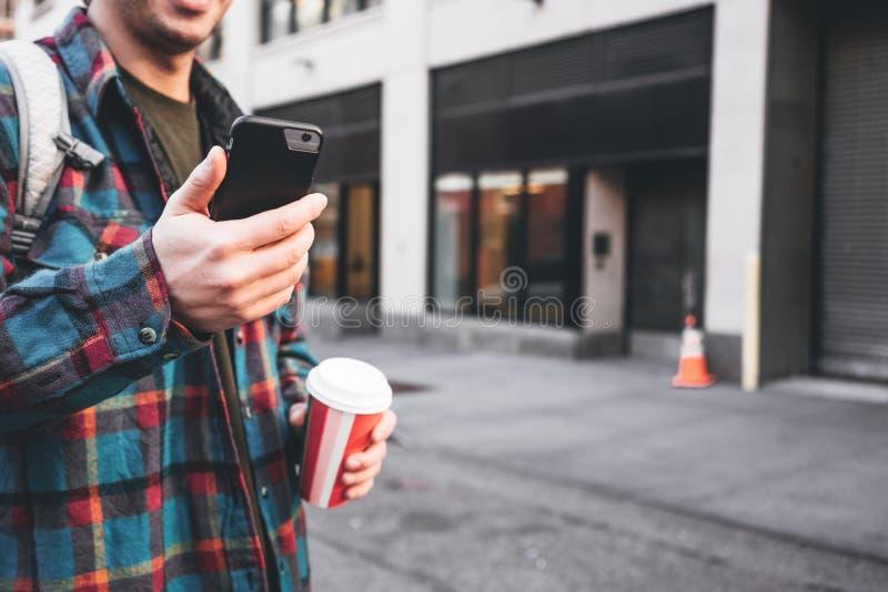 Homem novo ocasional que anda no copo da posse da rua da cidade do café quente à disposição e que usa o telefone celular para a r foto de stock royalty free