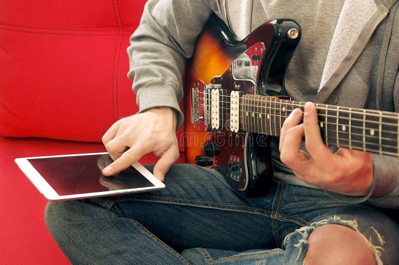 Homem novo ocasionalmente vestido com a guitarra que joga músicas na sala em casa Conceito em linha das lições da guitarra Pratic fotos de stock royalty free