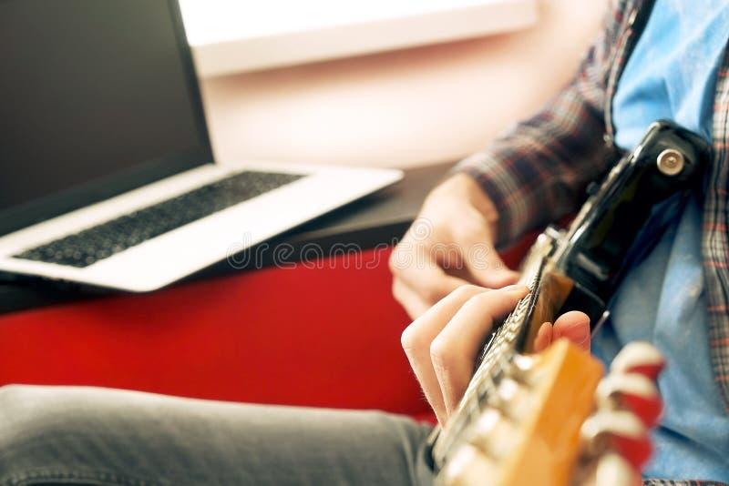 Homem novo ocasionalmente vestido com a guitarra que joga músicas na sala em casa Conceito em linha das lições da guitarra Pratic fotografia de stock