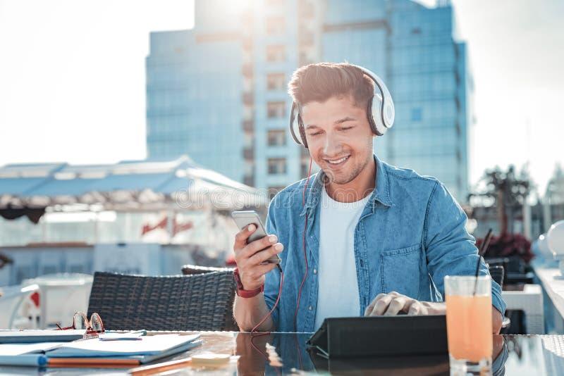 Homem novo ocupado positivo que escuta a música no café fotos de stock