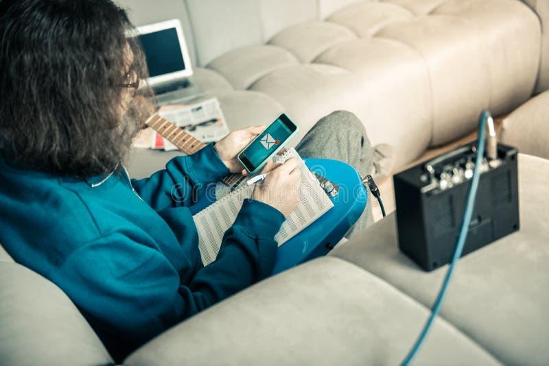 Homem novo ocupado que é músico profissional e que escreve para baixo notas imagem de stock royalty free