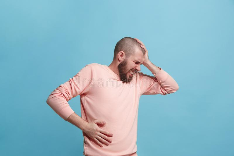 Homem novo oprimido com uma dor no estômago imagens de stock royalty free