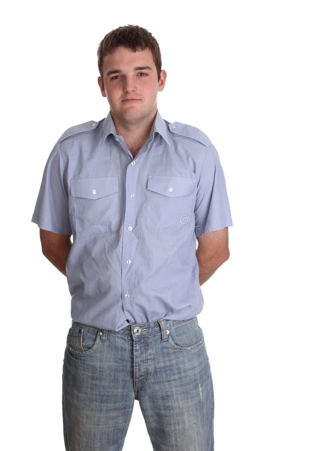 Homem novo ordinário em uma camisa azul e em calças de brim imagens de stock