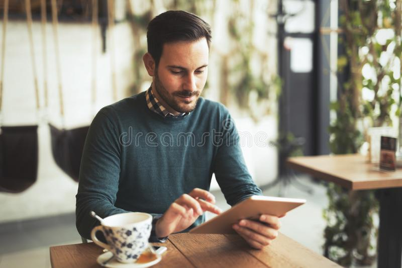 Homem novo ou estudante que usa o tablet pc no café imagem de stock