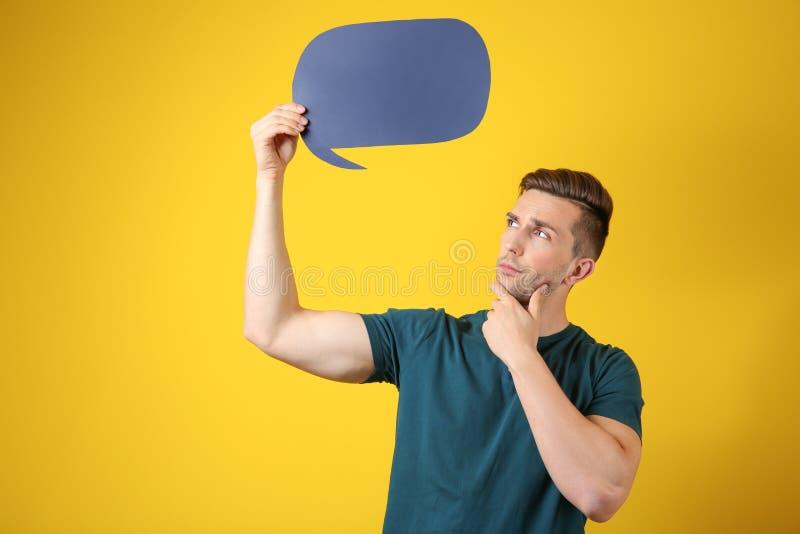 Homem novo pensativo com bolha do discurso no fundo da cor fotografia de stock