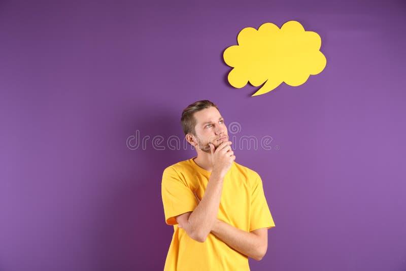 Homem novo pensativo e bolha vazia do discurso no fundo da cor foto de stock