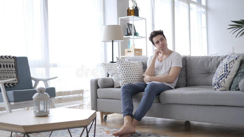 Homem novo pensativo que pensa ao sentar-se no sofá em casa imagens de stock royalty free