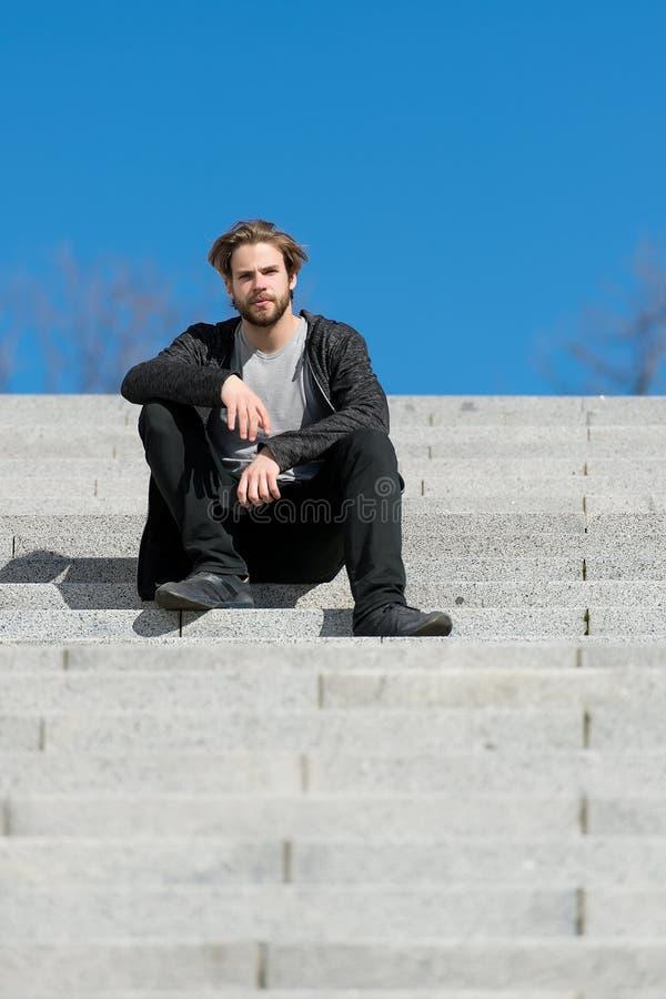 Homem novo pensativo que senta-se em etapas contra o fundo do céu azul imagem de stock royalty free
