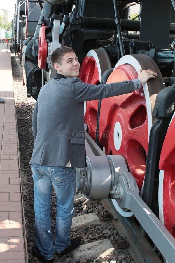 Homem novo perto da locomotiva imagem de stock