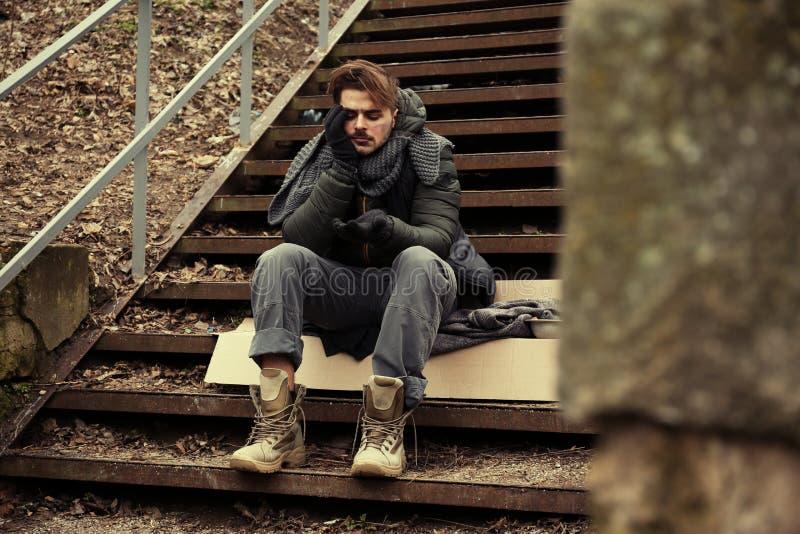 Homem novo pobre que senta-se em escadas fotos de stock royalty free