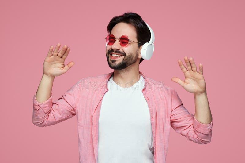 Homem novo positivo com os ?culos de sol, vestidos na roupa ? moda escutando a m?sica nos fones de ouvido modernos, isolados no c imagem de stock