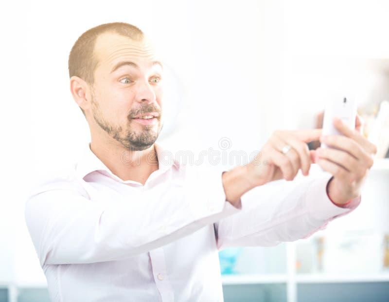 Homem novo positivo com smartphone imagem de stock