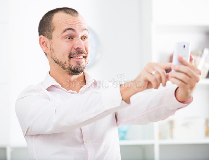 Homem novo positivo com smartphone fotografia de stock royalty free
