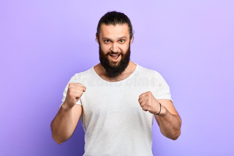 Homem novo positivo feliz que veste a roupa à moda que levanta com punhos apertados foto de stock