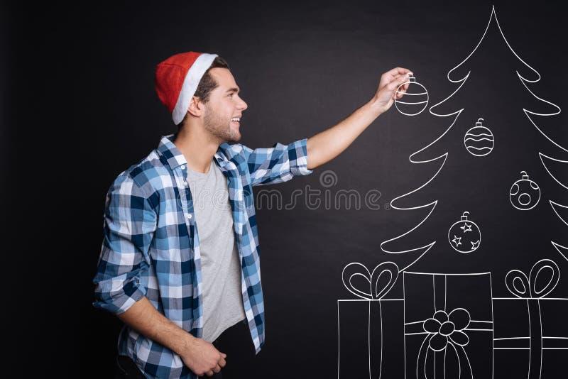 Homem novo positivo que decora uma árvore de Natal fotos de stock