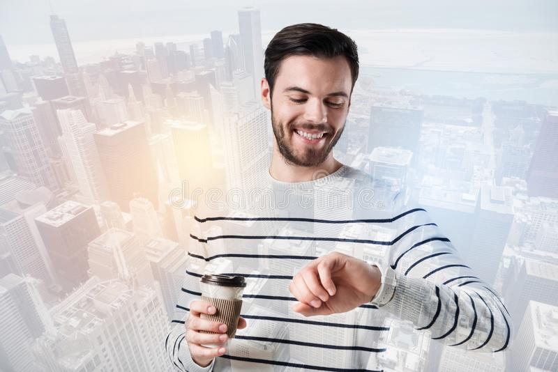 Homem novo positivo que olha seu relógio ao beber o café foto de stock