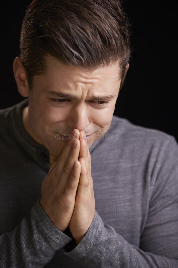 Homem novo preocupado com as mãos abraçadas, retrato vertical fotos de stock