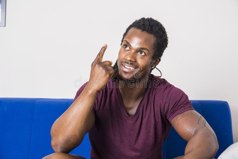 Homem novo preto que pensa uma ideia, fazendo a expressão engraçada imagens de stock royalty free