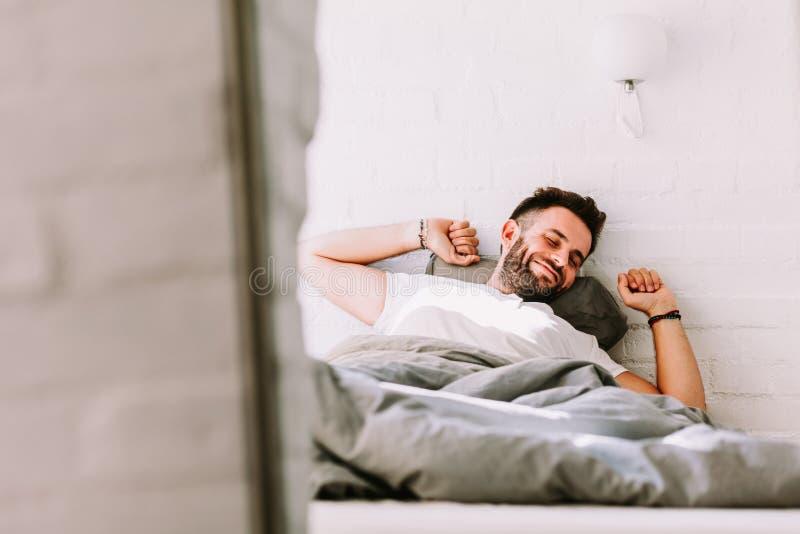 Homem novo que acorda na cama imagens de stock