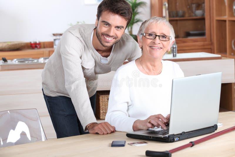 Homem novo que ajuda a mulher superior foto de stock royalty free
