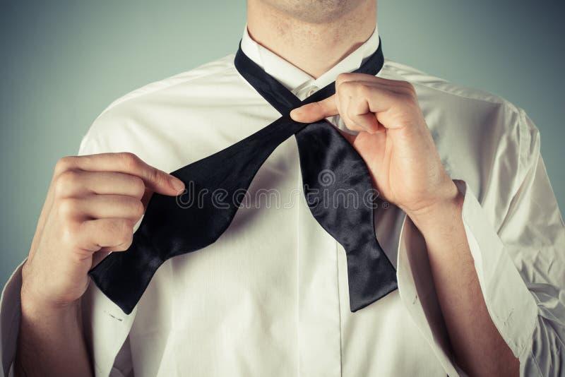 Homem novo que amarra um laço foto de stock