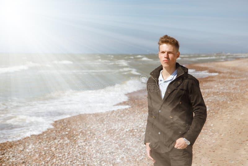 Homem novo que anda ao longo do litoral imagens de stock