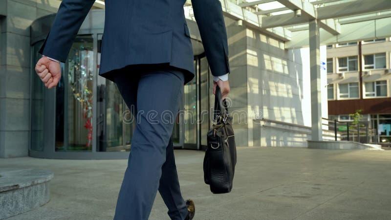 Homem novo que anda ao prédio de escritórios, começo do dia do trabalho, futuro bem sucedido foto de stock royalty free