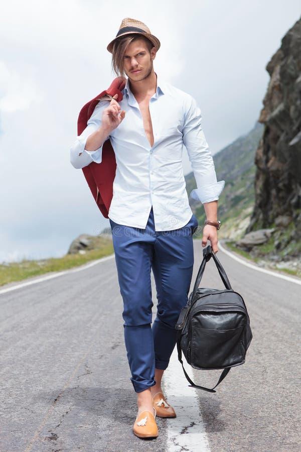 Homem novo que anda com o saco na estrada fotos de stock royalty free