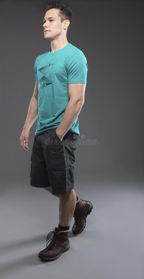 Homem novo que anda no short imagens de stock