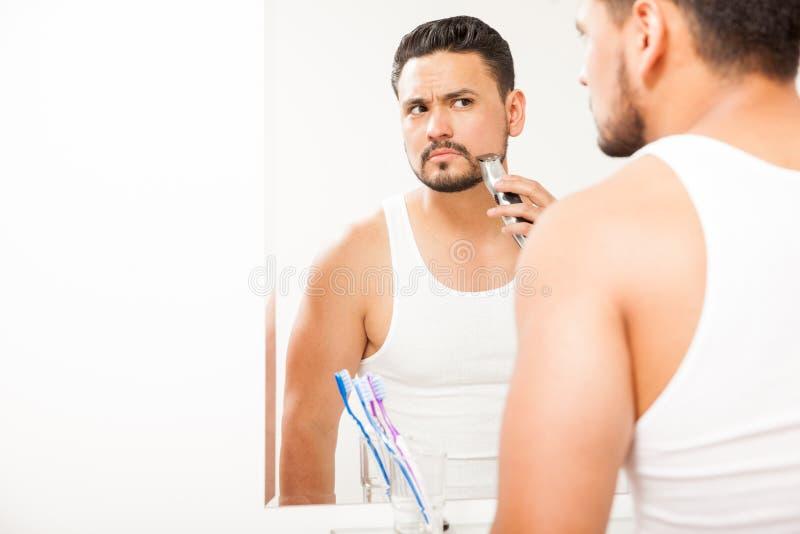 Homem novo que apara sua barba no banheiro fotos de stock