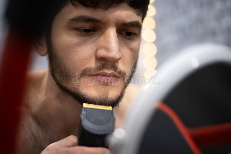 Homem novo que apara sua barba no espelho foto de stock
