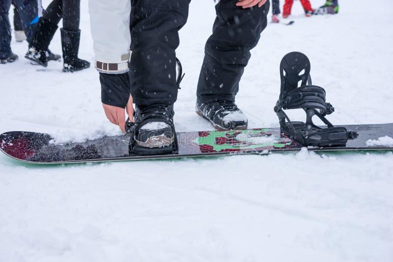 Homem novo que aperta as correias em seu snowboard imagem de stock royalty free