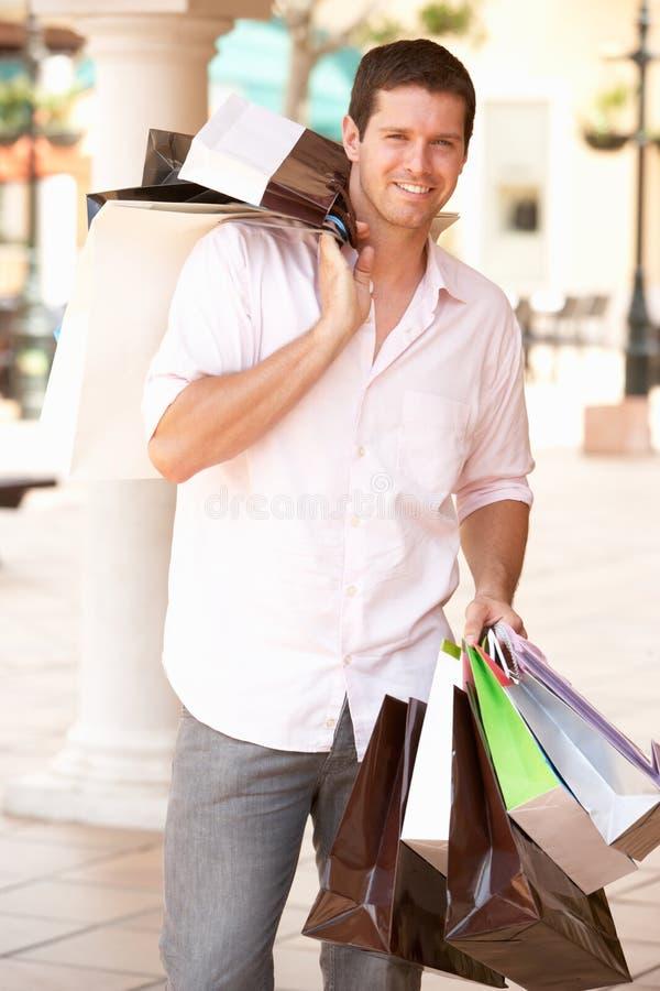 Homem novo que aprecia a compra imagem de stock