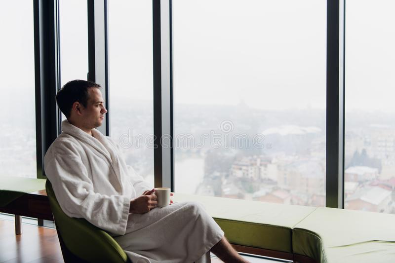 Homem novo que aprecia nivelando o café e a paisagem bonita do por do sol da cidade ao estar pela janela foto de stock
