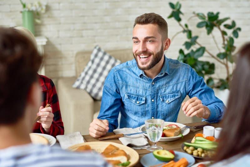 Homem novo que aprecia o jantar com amigos fotografia de stock