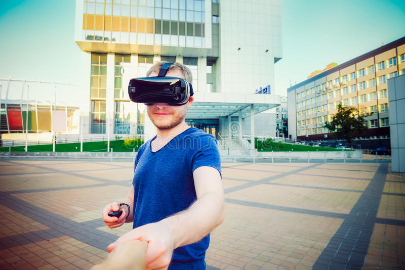 Homem novo que aprecia os vidros da realidade virtual que guardam a mão da amiga no fundo moderno da cidade Siga-me conceito da f imagens de stock royalty free