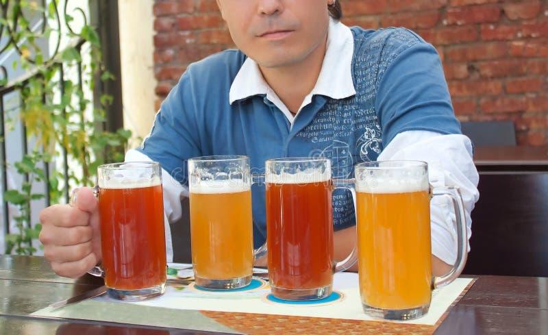 Homem novo que aprecia uma cerveja em uma barra foto de stock
