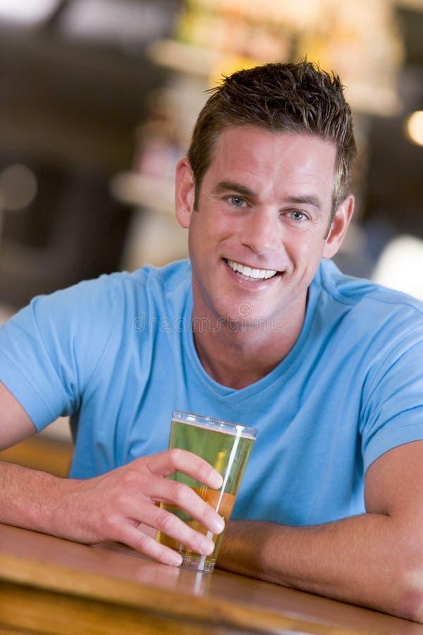 Homem novo que aprecia uma cerveja em uma barra foto de stock royalty free
