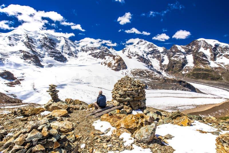 Homem novo que aprecia a vista impressionante da geleira de Morteratsch imagens de stock