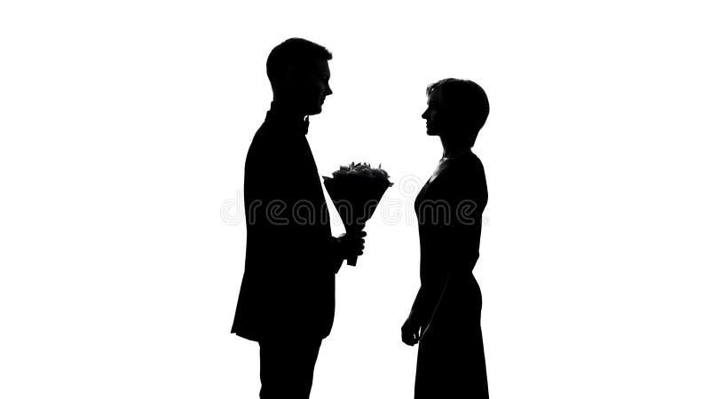 Homem novo que apresenta o ramalhete da flor da amiga, celebração do aniversário, primeira data imagens de stock