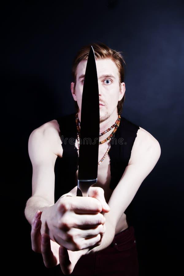 Homem novo que ataca com faca foto de stock